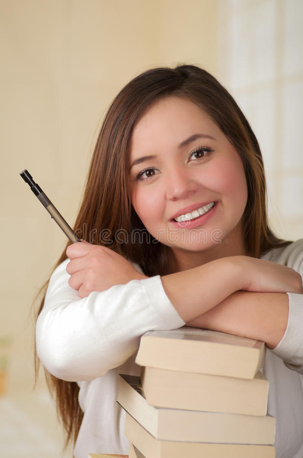Kobieta odpoczywa nad stosem książki zdjęcia stock