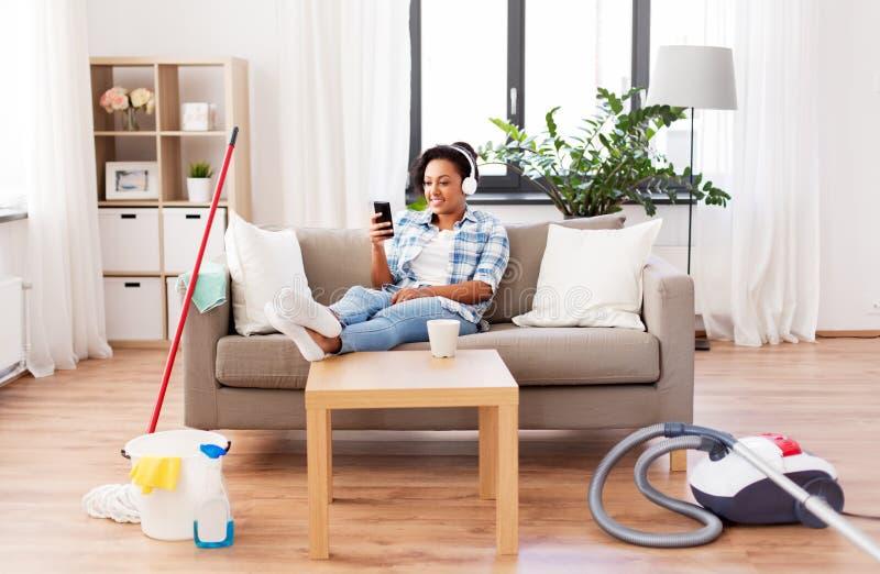 Kobieta odpoczywa po domowy czy?ci? w he?mofonach obraz royalty free