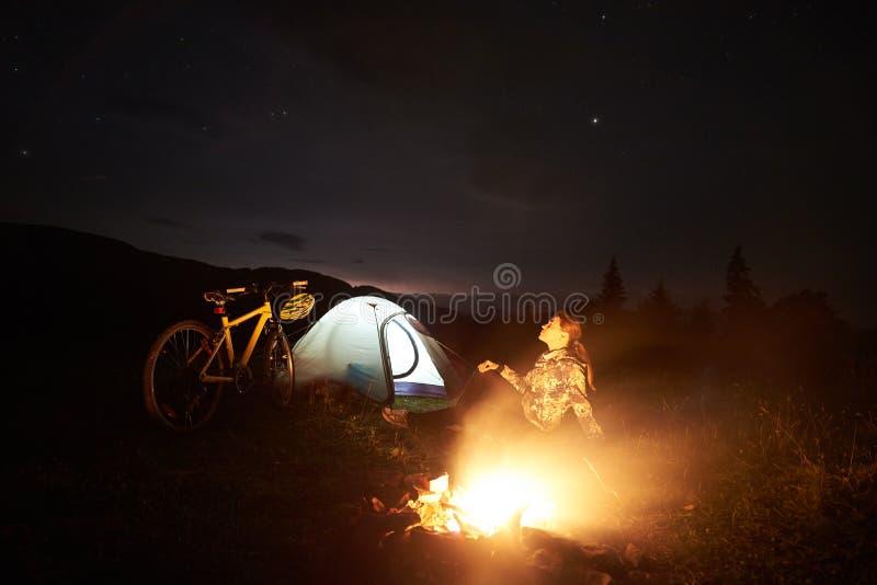 Kobieta odpoczywa przy nocą obozuje blisko ogniska, turystyczny namiot, bicykl pod wieczór niebem gwiazdy pełno zdjęcie royalty free