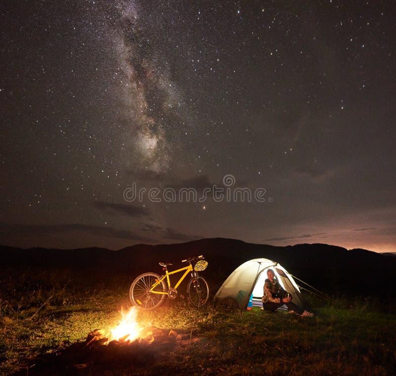 Kobieta odpoczywa przy noc? obozuje blisko ogniska, turystyczny namiot, bicykl pod wiecz?r niebem gwiazdy pe?no zdjęcie royalty free