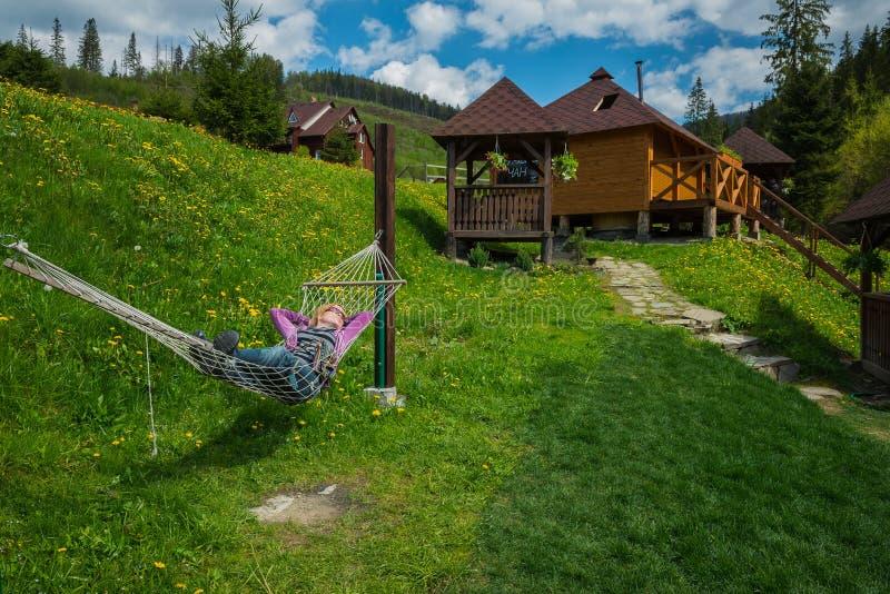 Kobieta odpoczywa w hamaku w górach drewniani domy na tle i zielonej trawie zdjęcie royalty free