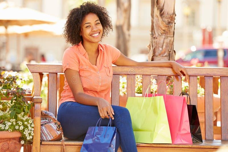Kobieta Odpoczywa Z torba na zakupy Siedzi W centrum handlowym obrazy royalty free