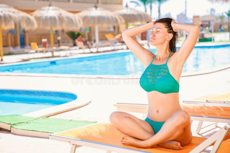 Kobieta odtwarza na lato plaży w pozy joga na lounger nad basenu tłem Powołanie i relaksować zdjęcie stock