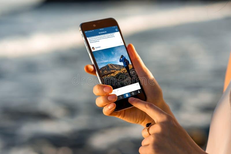 Kobieta ogląda Instagram wiadomość z nowym iPhone zdjęcia stock