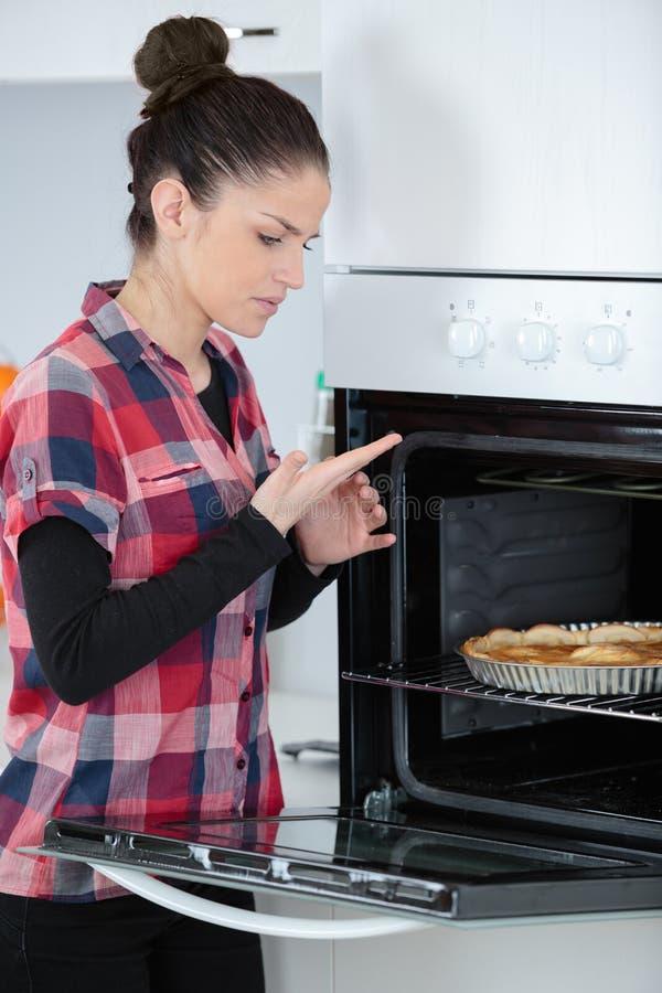 Kobieta ono palił wzruszający piekarnik obraz stock