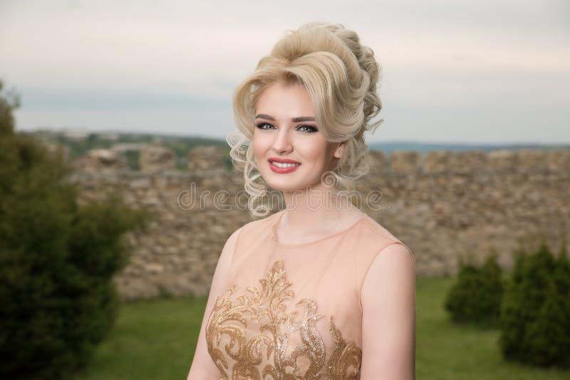 Kobieta ono uśmiecha się z fryzurą patrzejący kamerę i pozycji ścianę kamień w ogródzie z zielonymi drzewami blisko fotografia royalty free