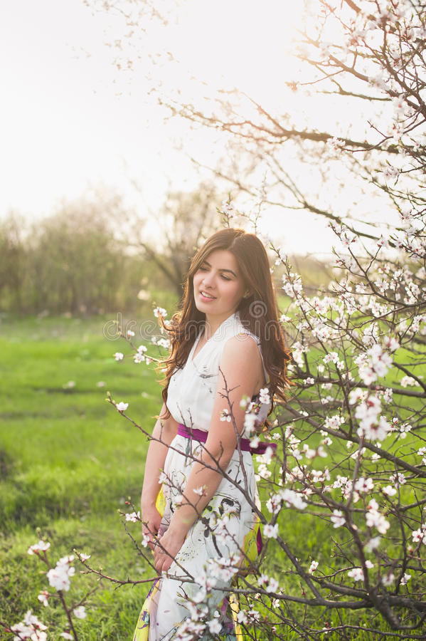 Kobieta ono uśmiecha się i raduje się z pięknym włosy w luksusowym wiosna ogródzie, piękno, makeup, włosy zdjęcie royalty free