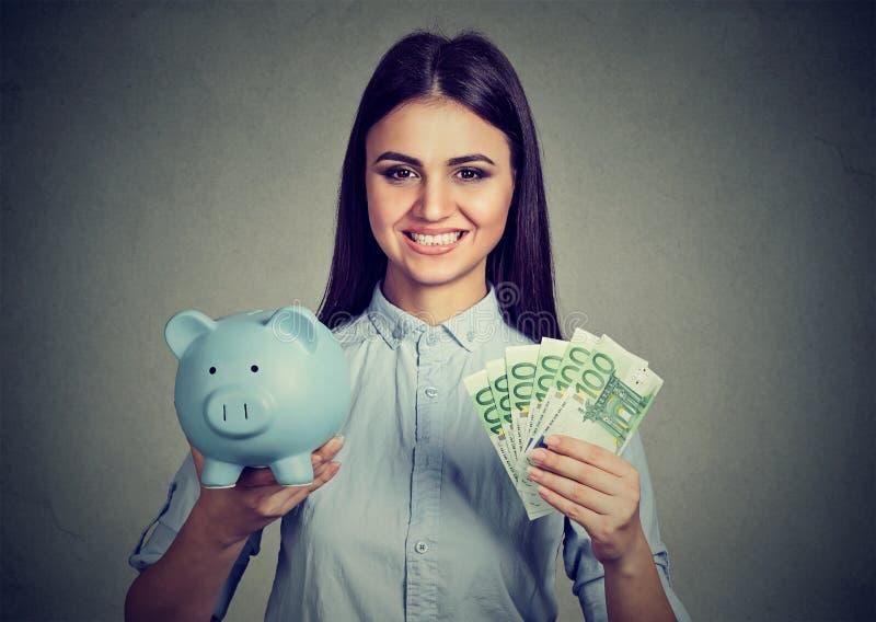 Kobieta ono uśmiecha się, trzymający prosiątko banka i sto euro banknotów zdjęcie stock