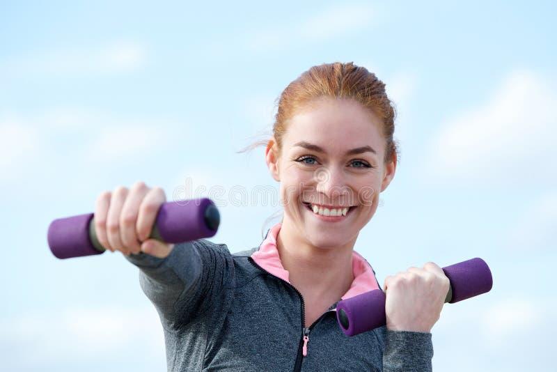 Kobieta ono uśmiecha się z aerobików ciężarami outdoors obrazy stock