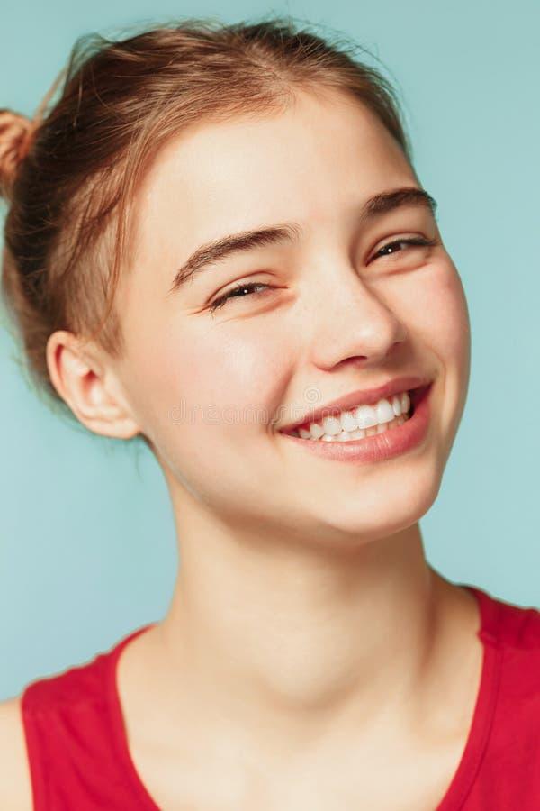 Kobieta ono uśmiecha się z perfect uśmiechem na błękitnym pracownianym tle i patrzeje kamerę fotografia stock