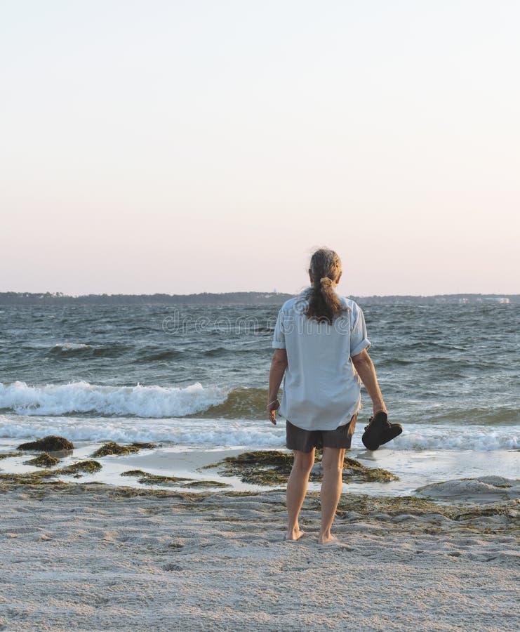 Kobieta ono Wpatruje się out morze na plaży przy świtem zdjęcia stock