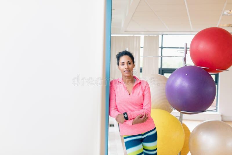 Kobieta opiera na ścianie w gym zdjęcie stock