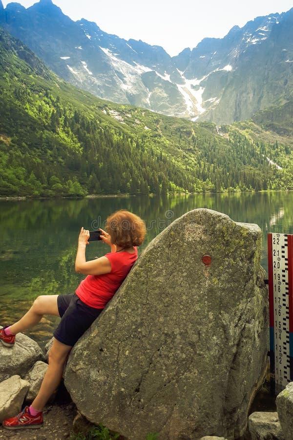 Kobieta opiera na kamieniu trzyma telefon w jej ręce i bierze obrazki «Denny oko «w Polska obrazy royalty free