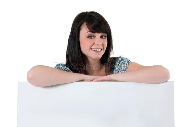Kobieta opiera na pustym znaku zdjęcia royalty free