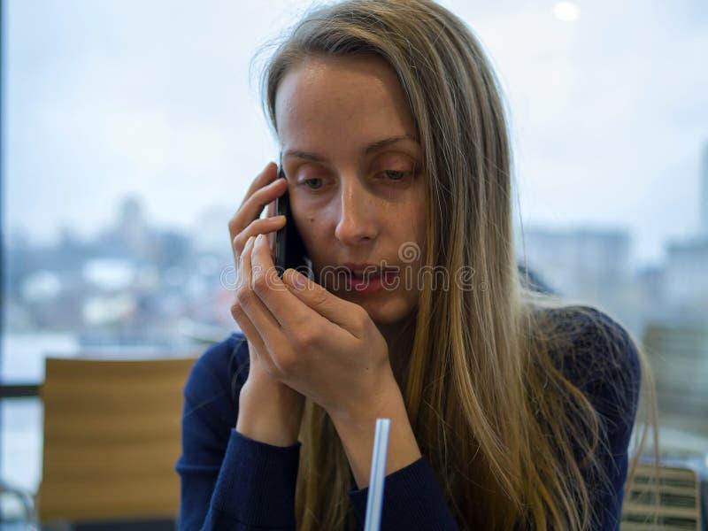 Kobieta opowiada smartphone w kawiarni obraz royalty free