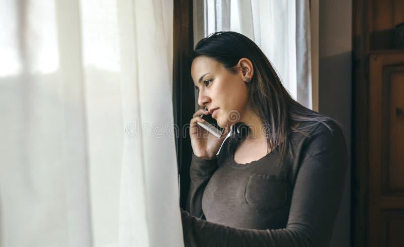 Kobieta opowiada telefon komórkowego i przyglądającego okno zdjęcie stock