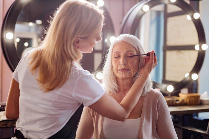Kobieta osobisty stylista stosuje tusz do rzęs jej rzęsy zdjęcie royalty free