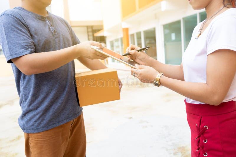 Kobieta otrzymywał pakuneczek od doręczeniowego pracownika Ładowacza mężczyzna przechodzi pudełka zdjęcie royalty free
