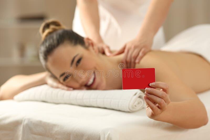 Kobieta otrzymywa masaż pokazuje kredytową kartę zdjęcie royalty free