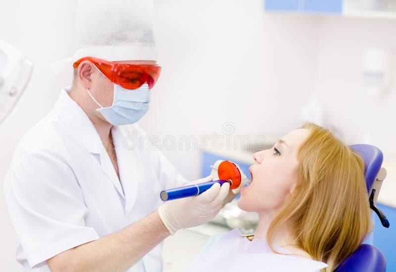 Kobieta otrzymywa stomatologicznego podsadzkowego suszarniczego proc z otwartym usta obrazy stock