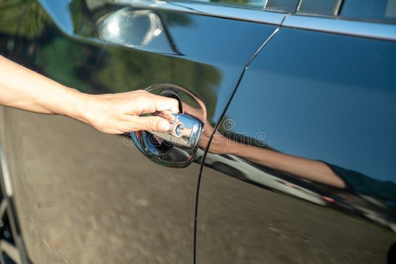 Kobieta otwiera drzwi jej nowy czarny samochód kupował samochód przy przedstawicielstwem handlowym zdjęcia stock