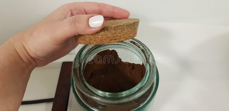Kobieta otwiera korek pokrywę szklany puchar z czarną kawą obraz royalty free