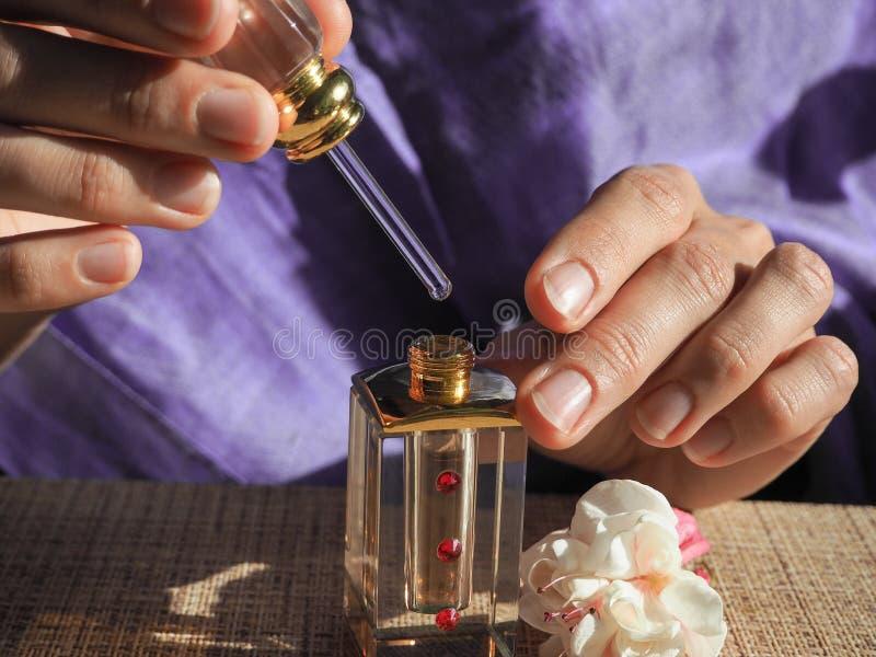 Kobieta otwiera pachnidło olej Perfumowy olej w kobiety ` s nadgarstkach Arabski pachnidło olej obraz royalty free