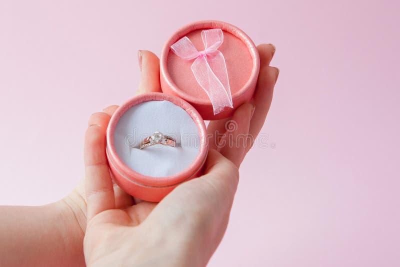 Kobieta otwiera prezenta pudełko z jewellery Obrączka ślubna w pudełku w rękach kobiety na różowym tle zdjęcie stock