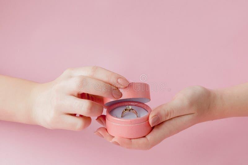 Kobieta otwiera prezenta pudełko z jewellery Obrączka ślubna w pudełku w rękach kobiety na różowym tle fotografia royalty free