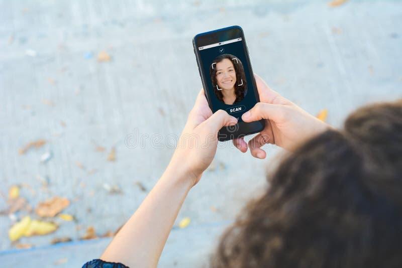 Kobieta otwiera smartphone z twarzową rozpoznanie technologią fotografia royalty free
