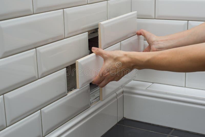 Kobieta otwiera, zamyka chowanego przeglądu sanitarnego ląg na ścianie płytka pod łazienką, obrazy stock