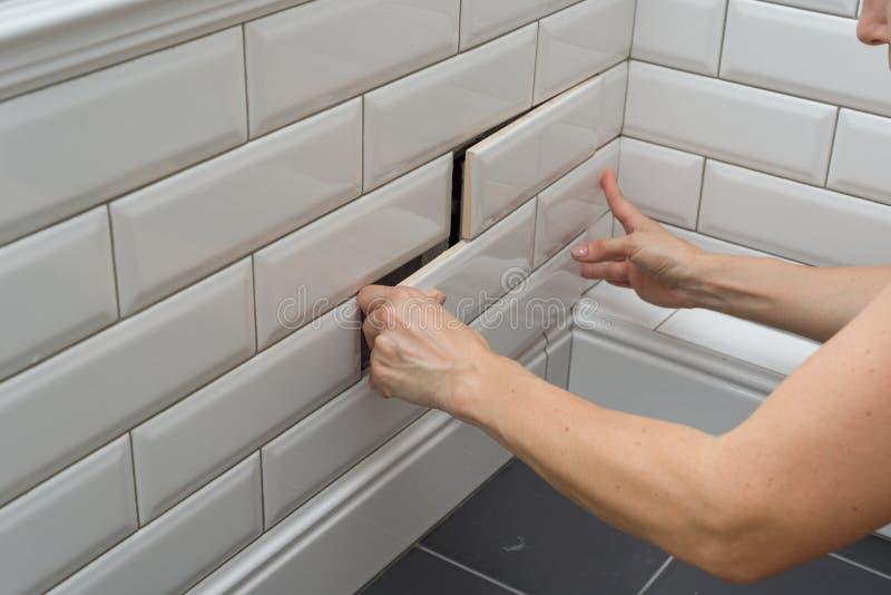 Kobieta otwiera, zamyka chowanego przeglądu sanitarnego ląg na ścianie płytka pod łazienką, obraz royalty free