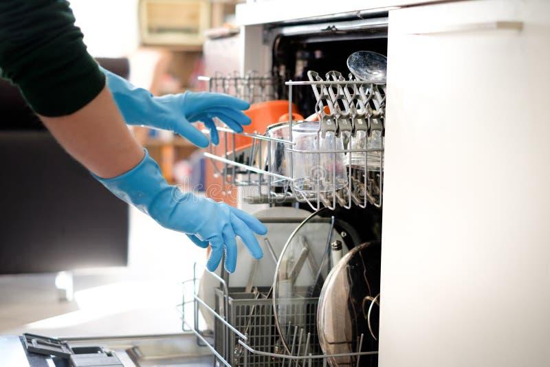 Kobieta otwiera zmywarka do naczyń w kuchni zdjęcie royalty free