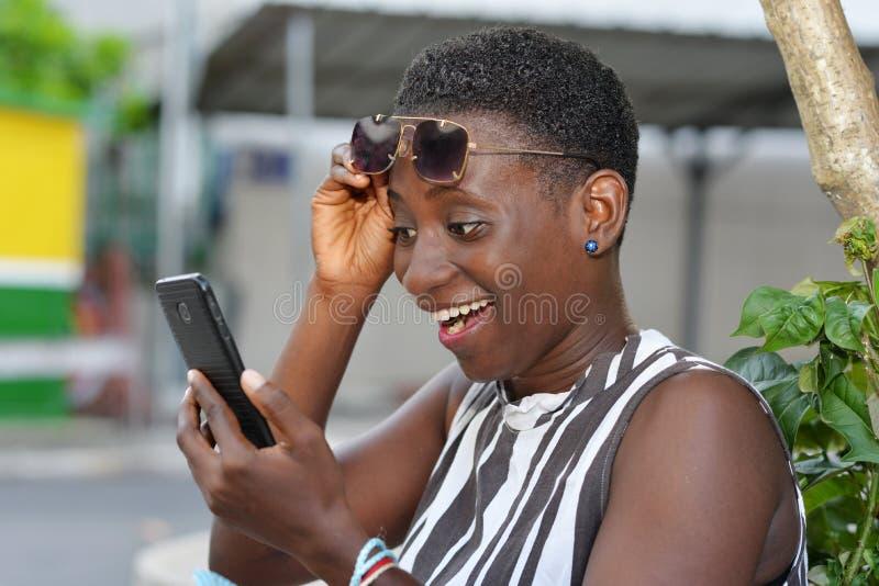 Kobieta outdoors używa telefonu komórkowego zastosowanie dla online zakupy fotografia stock