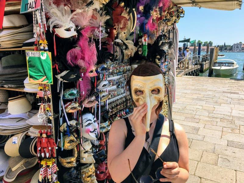 Kobieta outside wzdłuż kanał grande w Wenecja, Włochy próbuje na venetian masce przy lokalnym plenerowym sprzedawcą zdjęcia stock