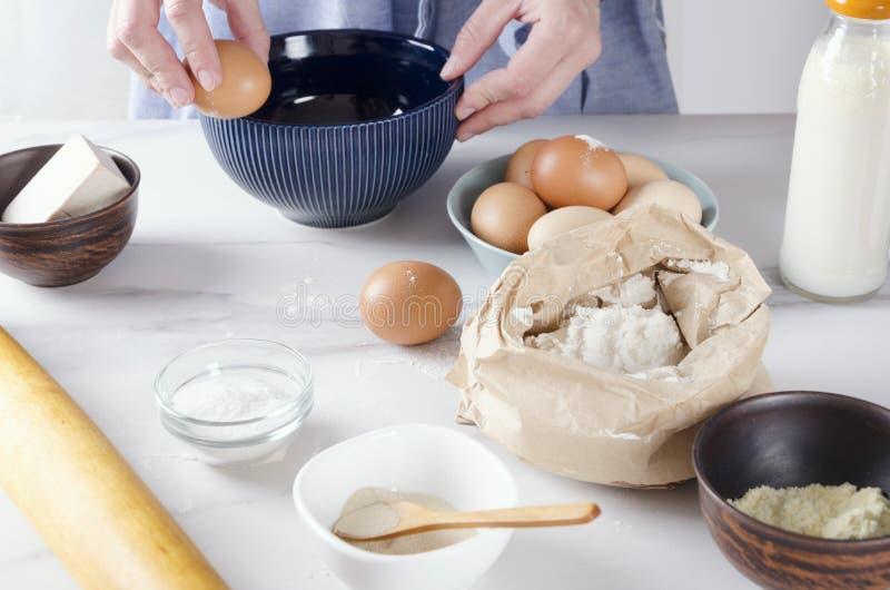 Kobieta pęka jajko w błękitnego puchar, piec torta proces Podstawowi składniki dla piec na kuchennym stole obraz stock