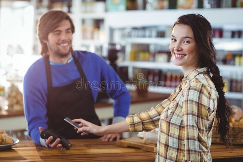 Kobieta płaci rachunek przez smartphone używać nfc technologię zdjęcie royalty free