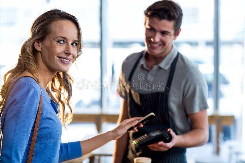 Kobieta płaci rachunek przez smartphone używać nfc technologię fotografia stock