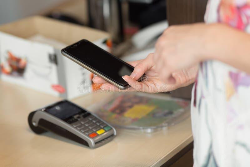 Kobieta płaci rachunek przez smartphone używać nfc technologię w kawiarni obraz stock