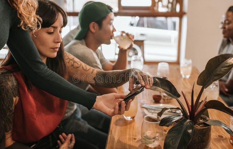 Kobieta płaci rachunek z jej smartphone w bistrze zdjęcia royalty free