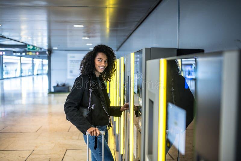 Kobieta płaci w parking maszynie w lotnisku z suitca obraz stock