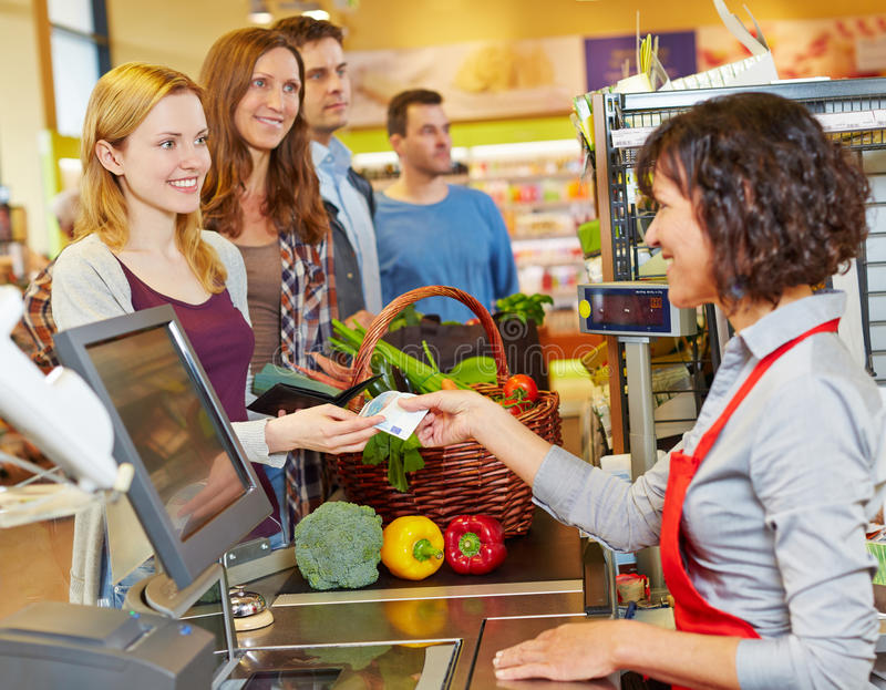 Kobieta płaci z pieniądze rachunkiem przy zdjęcie stock