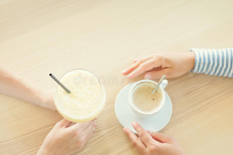 Kobieta para pijąca kawę i koktajl w kawiarni fotografia royalty free