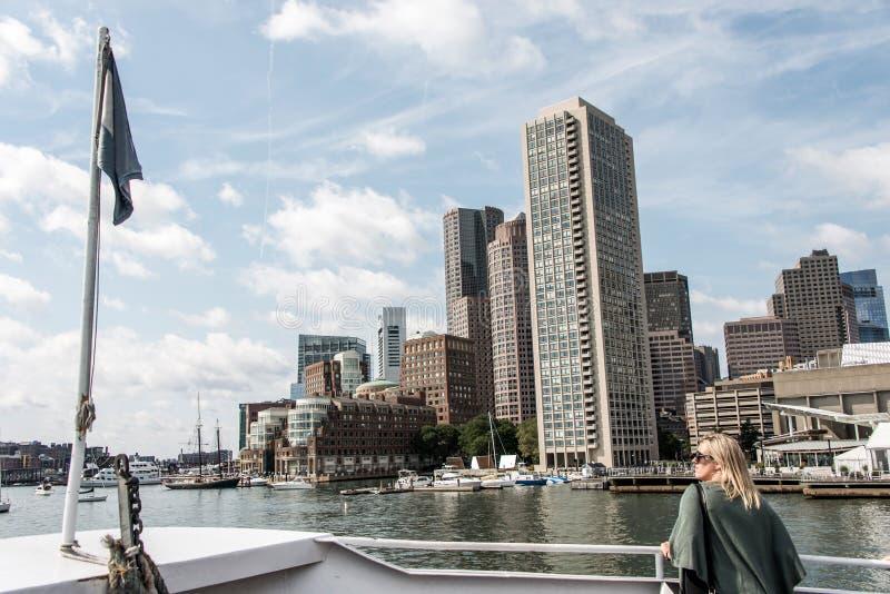 Kobieta patrzeje żeglowanie łodzie na Charles rzece przed Boston linią horyzontu na pogodnym letnim dniu na promu zdjęcia stock