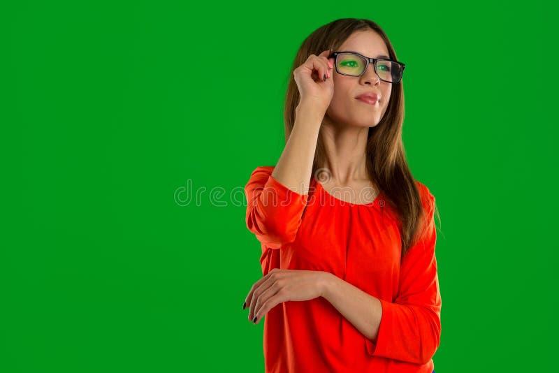 Kobieta patrzeje daleko od w szkłach na zielonym tle obraz stock