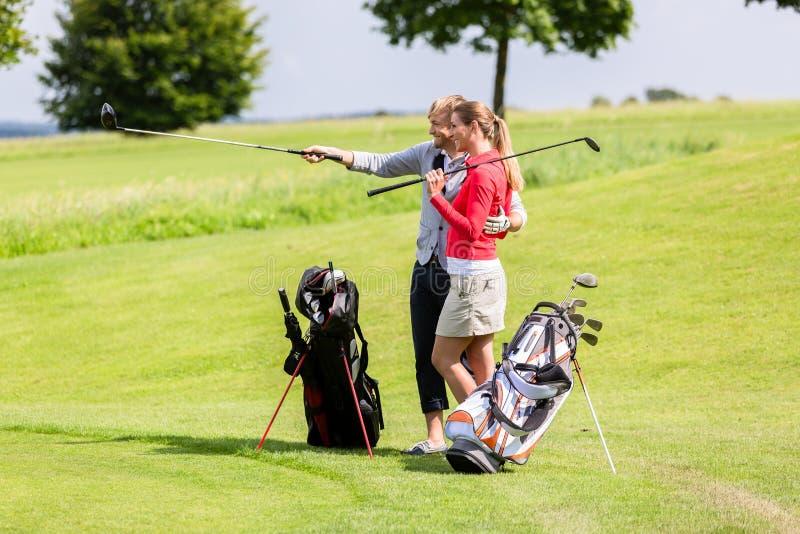 Kobieta patrzeje jego chłopak pozycję na polu golfowym zdjęcie royalty free