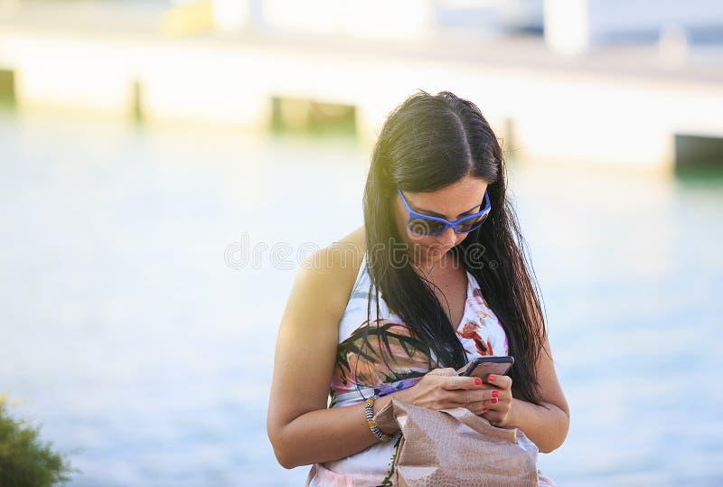 Kobieta patrzeje jej mądrze telefon obrazy royalty free