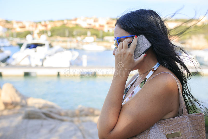 Kobieta patrzeje jej mądrze telefon obraz stock