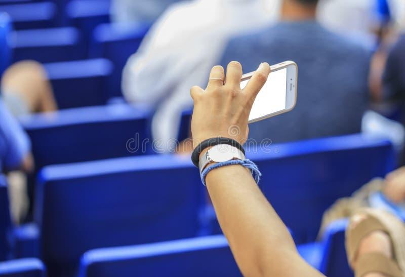 Kobieta patrzeje jej mądrze telefon zdjęcie stock