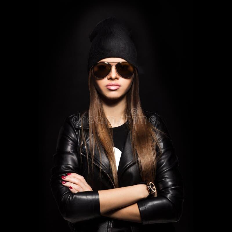 Kobieta patrzeje kamerę na czarnym tle w okularach przeciwsłonecznych fotografia stock
